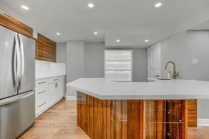 basement kitchen with amazing back lit cabinets and glass sheves in round island