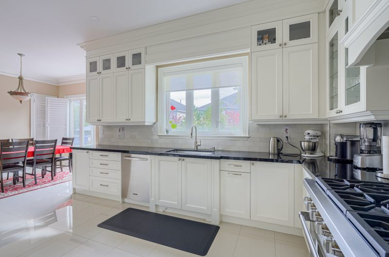 amazing kitchen with crown moudling trim and glass cabinet doors - kitchen design aurora