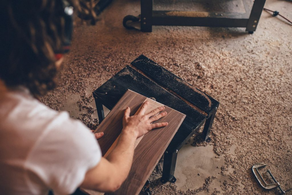 photo of a man cuts wooden panel